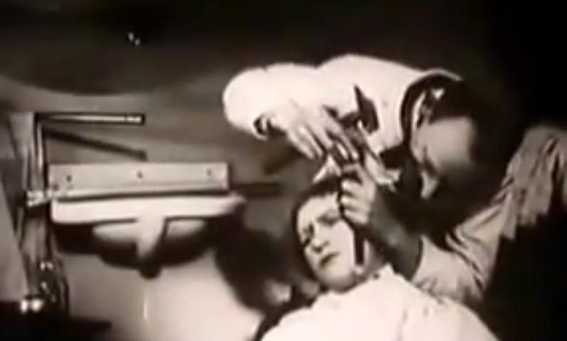 """Karl Valentin elimina una verruca dal viso di Liesl Karlstadt con uno scalpello, nel film """"Mysterien eines Frisiersalons"""" (1922)"""